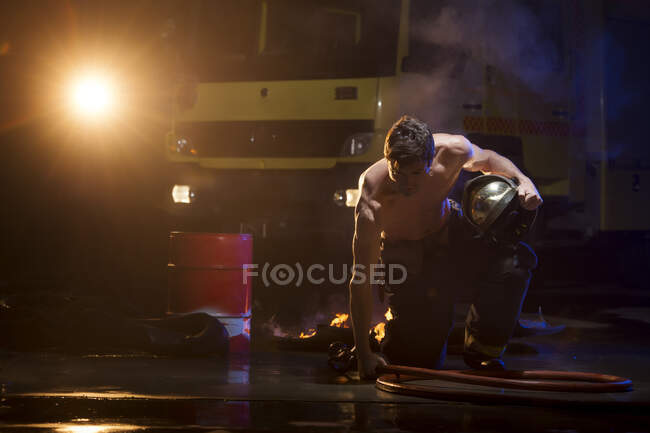 Shirtless muscular male in fireman uniform sitting on burning floor during dangerous mission — Stockfoto