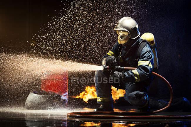 Анонімний пожежник, що б'ється з водою. — стокове фото