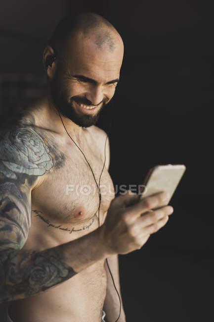 Atleta calvo senza maglietta che sorride e naviga sullo smartphone mentre si trova in una palestra buia e ascolta musica durante l'allenamento — Foto stock