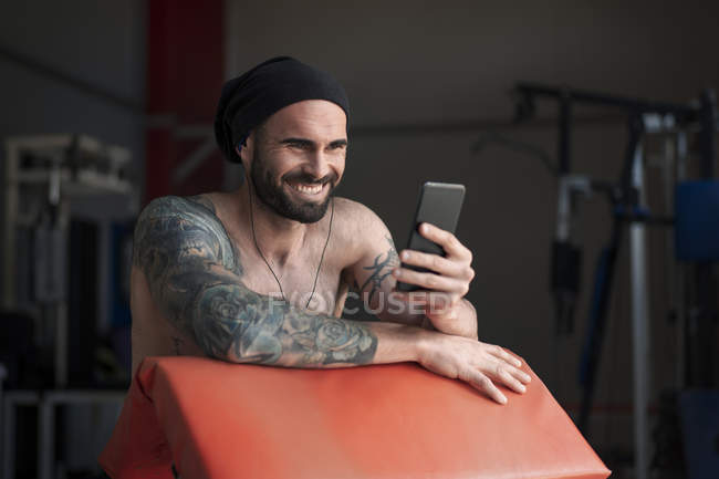 Laughing shirtless tattooed athlete with smartphone in gym — Stock Photo