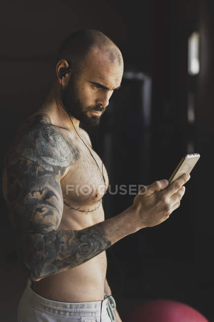 Лысый татуированный спортсмен с помощью смартфона в тренажерном зале — стоковое фото