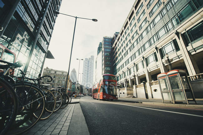 Red bus and bicycle parking on city street in London — Stock Photo