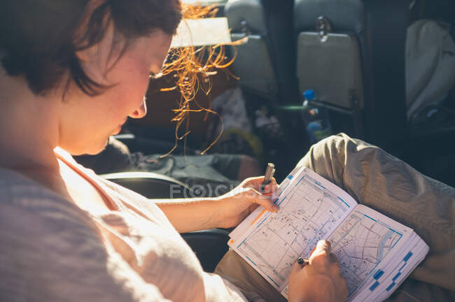 From above woman writing on map while sitting on comfortable seat during trip through Thailand — Stock Photo