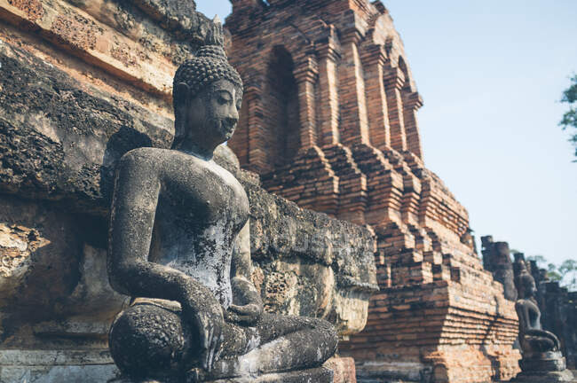 Weathered statue of Buddha located near shabby stone walls of ancient oriental temple in Thailand — Stockfoto