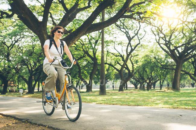 Красуня в повсякденному одязі їздить сучасним велосипедом на стежці біля зелених дерев у прекрасному парку в сонячний день — стокове фото
