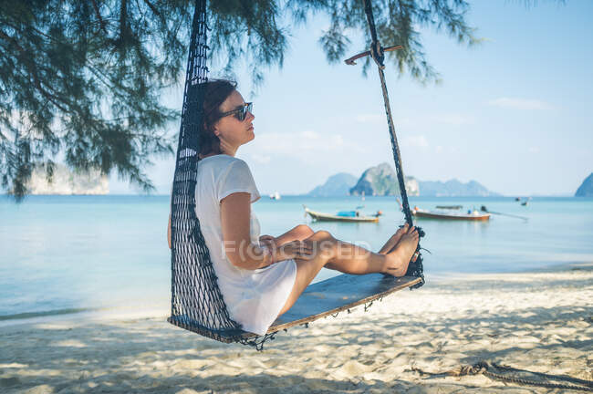 Side view of pretty female relaxing in hammock near calm sea on sandy beach in Thailand — Stock Photo
