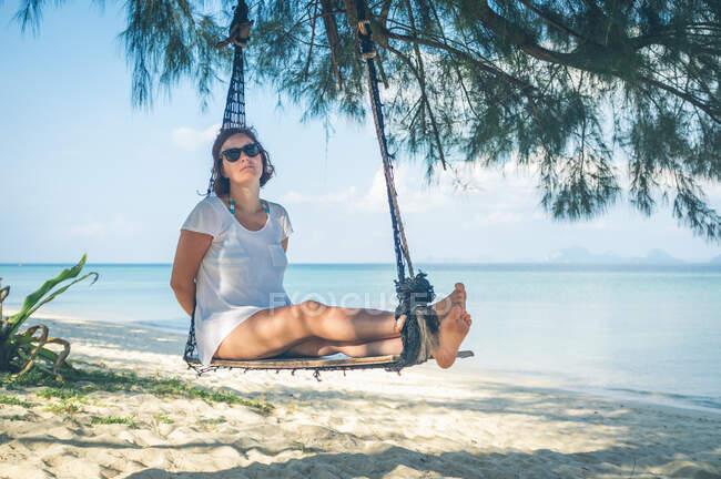 Woman in hammock near sea — стокове фото