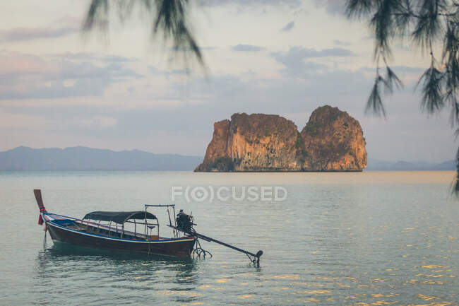 Small fishing boat floating on surface of tranquil sea water in beautiful morning in Thailand — Stock Photo