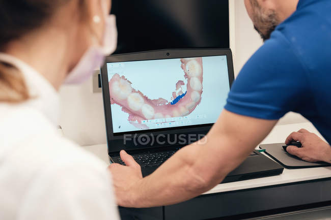 Anonymous man demonstrating teeth scan on laptop screen to unrecognizable female dentist in modern clinic — Stock Photo