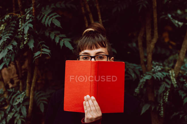 Young elegant woman in eyeglasses looking at camera while covering face with book in city garden — Stock Photo