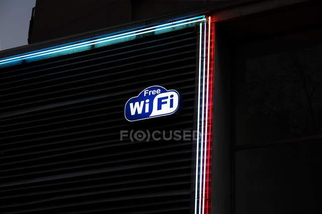 Pegatina Wi Fi gratis adjunta a la pared del edificio cerca de luces de neón en la calle de la ciudad por la noche - foto de stock