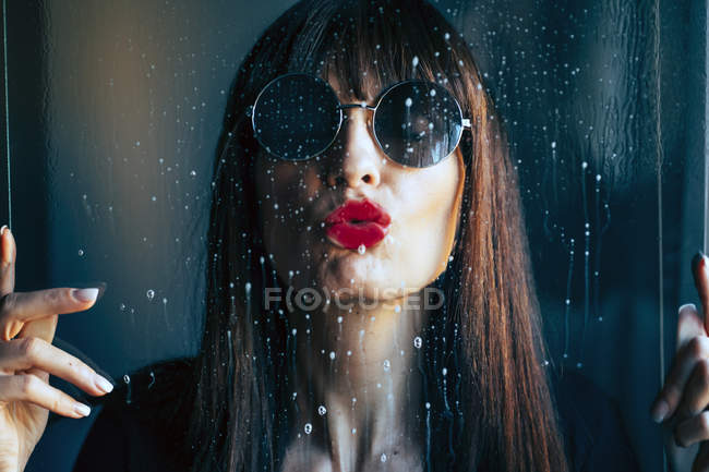 Attractive female with red lips kissing clean transparent glass passionately — Stock Photo