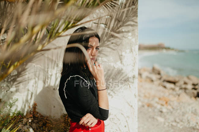 Jeune femme brune debout près de feuilles de palmier tropicales sur la côte — Photo de stock