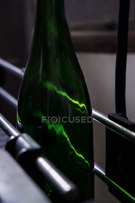 Sealed green bottle of wine moving on modern transporter belt in winery — Stock Photo