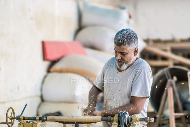 Mann benutzt Holzbearbeitungsmaschine am Arbeitsplatz — Stockfoto