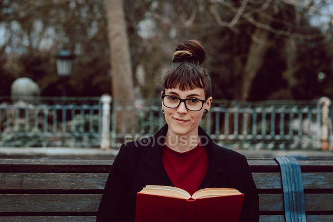 Young elegant woman in eyeglasses reading book and sitting on bench in city garden — Stock Photo