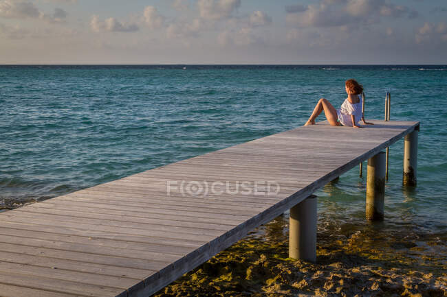 Side view of pretty young female looking away while sitting on wooden pier near rippled sea water against cloudy evening sky in Maldives — Stock Photo
