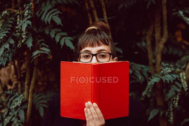 Молодая элегантная женщина в очках смотрит в камеру, закрывая лицо книгой в городском саду — стоковое фото