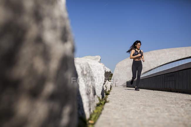 Юная брюнетка стройная женщина в спортивной одежде бегает в парке в солнечный день — стоковое фото