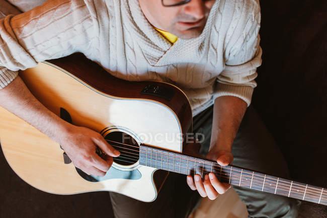 Nahaufnahme eines Mannes, der auf dunklem Hintergrund Gitarre spielt — Stockfoto