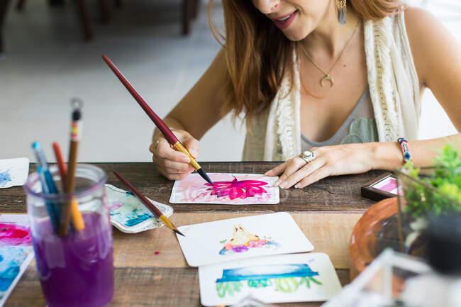 Artista latina pintando con acuarela en su estudio - foto de stock