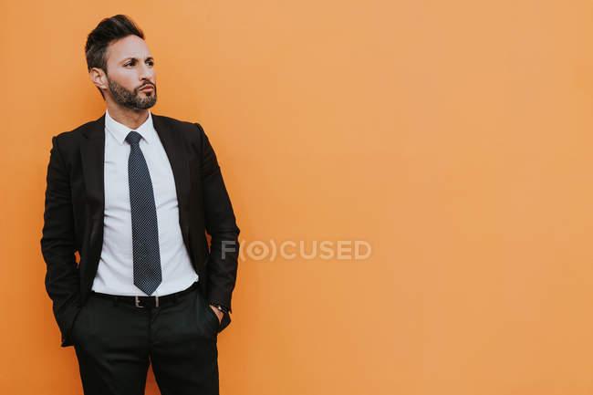 Взрослый красивый элегантный бизнесмен в официальном костюме смотрит в камеру возле оранжевой стены — стоковое фото