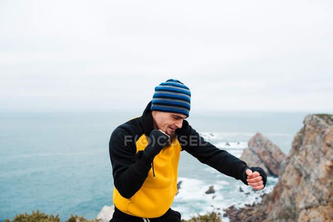 Hombre barbudo adulto en ropa deportiva practicando golpes durante el entrenamiento de kickboxing en un acantilado rocoso cerca del mar - foto de stock