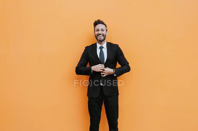 Взрослый красивый элегантный бизнесмен в формальном костюме, корректируя пиджак и глядя в камеру у оранжевой стены — стоковое фото
