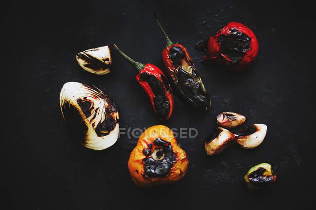 Roasted vegetables scattered on black background — Stock Photo