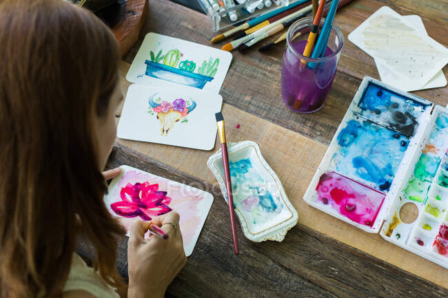 Latin artist painting with watercolor in her studio — Stock Photo