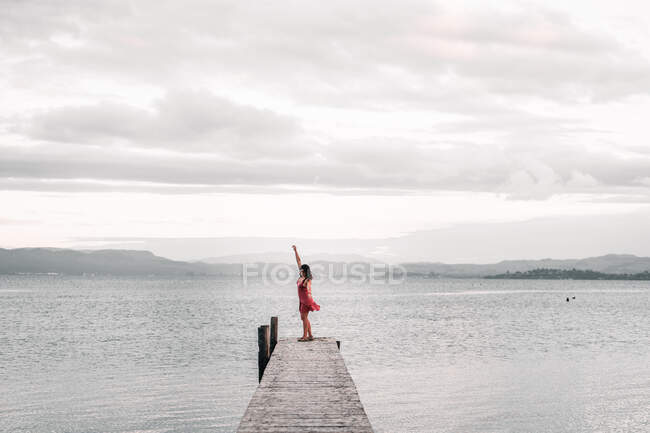 Woman posing on pier near wonderful lake — стокове фото