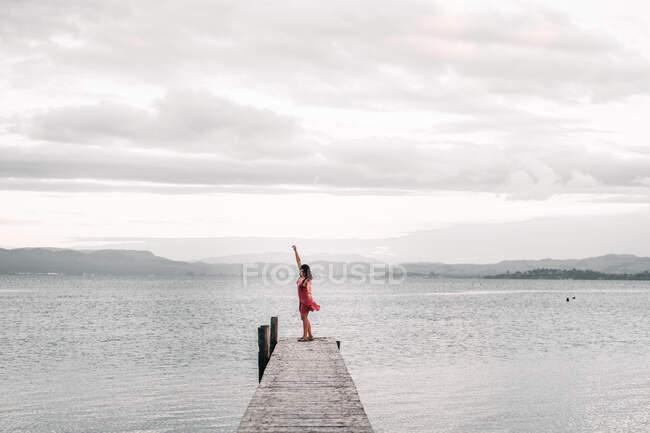 Жінка на пірсі біля чудового озера. — стокове фото