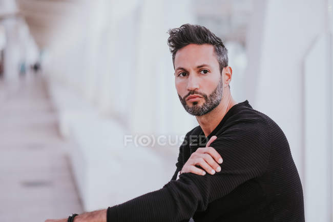 Adult handsome elegant cheerful male in casual wear looking at camera on city street — Stock Photo