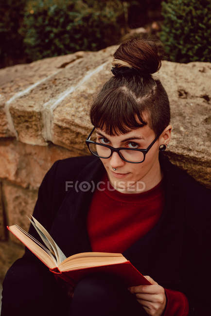 Young elegant woman in eyeglasses leaning on stone wall with book and looking at camera — Stock Photo