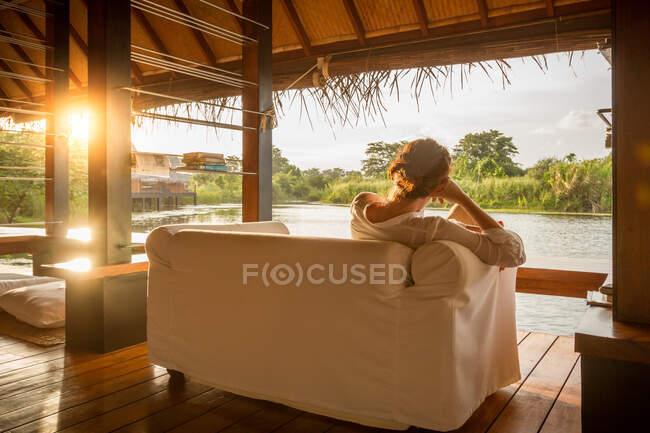 Жінка сидить на дивані і дивиться на спокійне озеро. — стокове фото