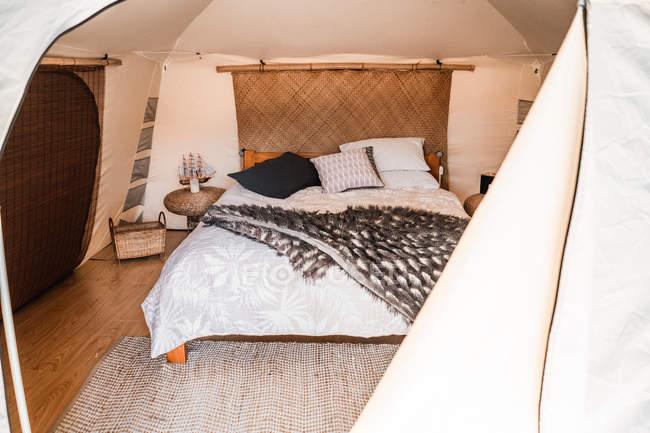 Komfortables Schlafzimmer mit Matte im großen Bett im Zelt — Stockfoto