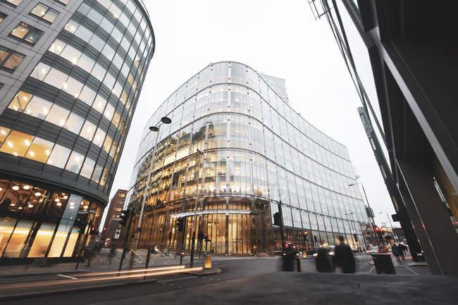 Larga exposición del nuevo edificio moderno con fachada de vidrio y luces en la calle en Londres, Reino Unido - foto de stock