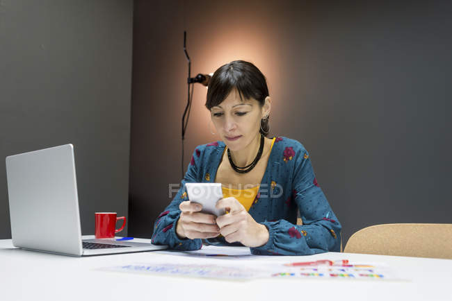 Businesswoman using smartphone near laptop while working in modern office — Stock Photo