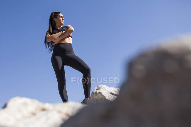 Young brunette woman in sportswear with crossed hands posing on rocks in sunny day — Stock Photo