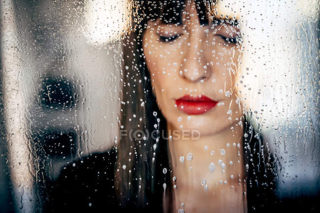 Attractive female with red lips behind clean transparent glass passionately — Stock Photo