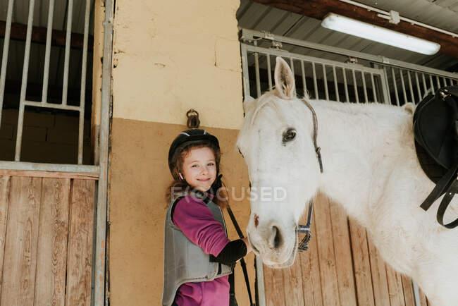Menina bonito no capacete com um cavalo branco sorrindo olhando para a câmera enquanto estava perto de barracas no estábulo durante a aula de equitação no rancho — Fotografia de Stock