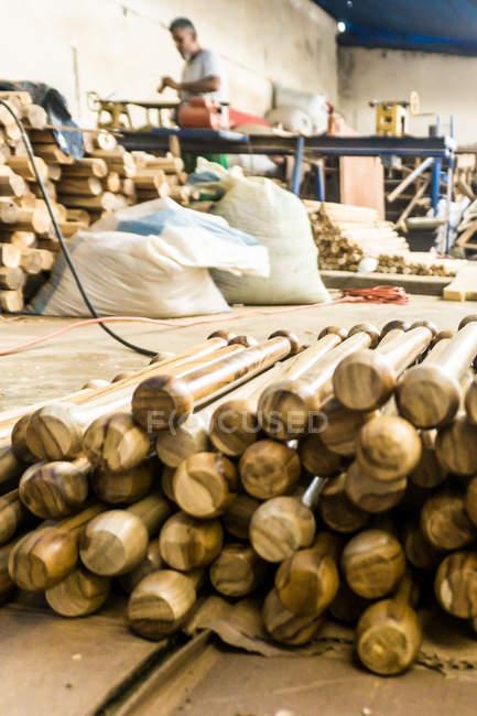 Tas de bâtons de bois sur le lieu de travail et charpentier travaillant sur le fond — Photo de stock