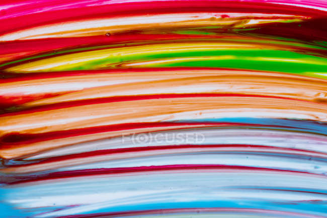 Multicolored brush strokes of acrylic colors on white canvas — Stock Photo
