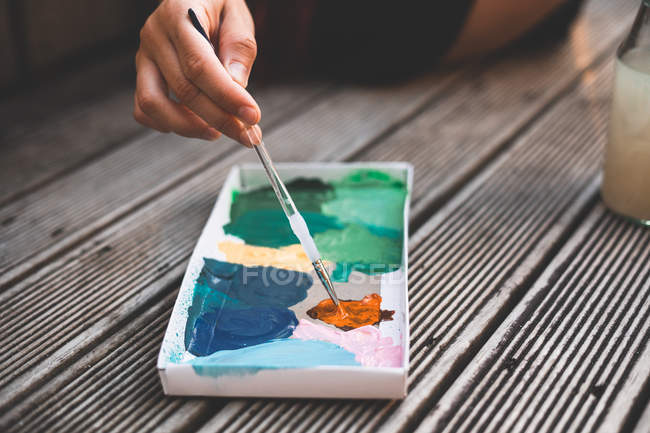 Closeup hand of artist using brush to mix paint in carton box while spending time on terrace — Stock Photo