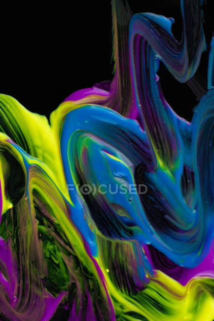 Spills of thick pigment of various colors mixing on black background — Stock Photo
