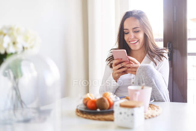 Attractive young happy woman using mobile phone and having breakfast at table near window at home — Stock Photo