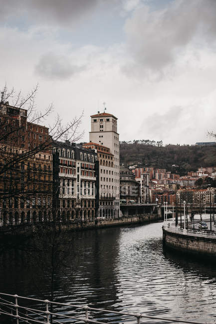Gray clouds floating on sky over old buildings and canal with rippled water on dull day in Bilbao, Spain — Stock Photo