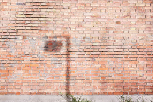 Shadow of pole with signboard on weathered brick wall on sunny day on city street — Stock Photo