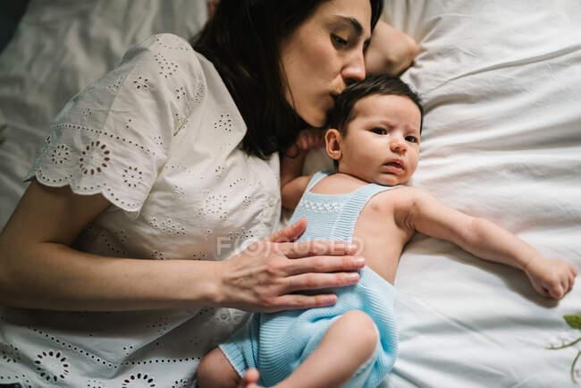 Madre y bebé acostados en la cama - foto de stock