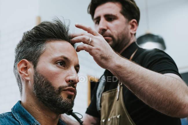 Da sotto barbiere pettinando capelli di bel maschio elegante seduto in barbiere — Foto stock